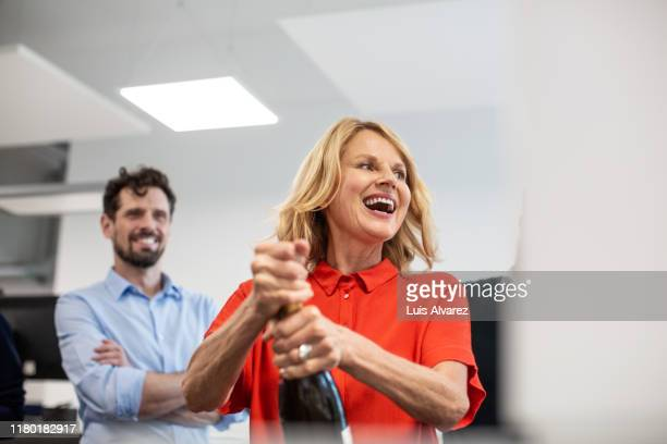 businesswoman opening champagne bottle in office - promotion employment stock pictures, royalty-free photos & images