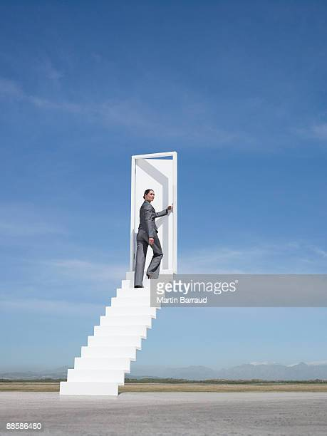 Businesswoman opening door at end of stairway leading to the sky