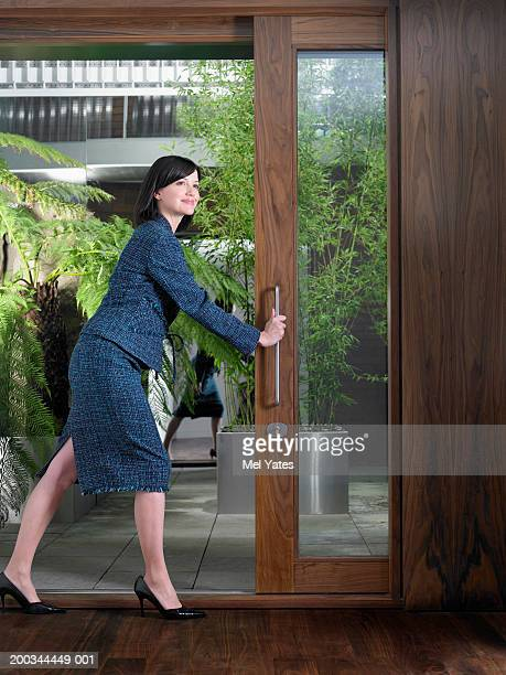 Businesswoman opening door, smiling, looking into distance