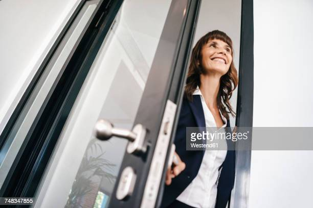 Businesswoman opening glass door