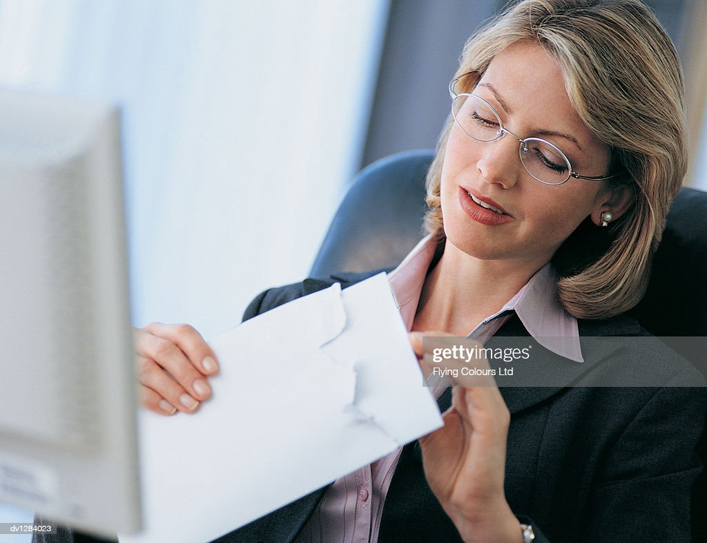 Businesswoman Opening Her Mail at Her Desk : Stock Photo