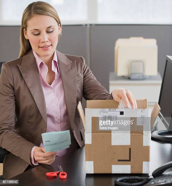 Businesswoman opening package