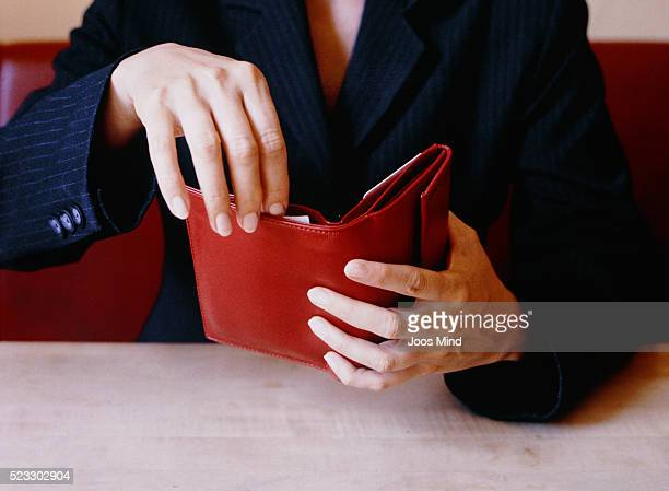 Businesswoman Opening Red Wallet at Table