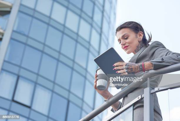 Businesswoman outdoors, holding coffee cup, using digital tablet, tattoos on hands, low angle view