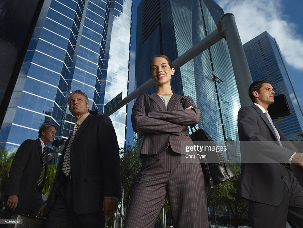 Businesswoman outdoors looking at camera with three businesspeople around her : Stock Photo