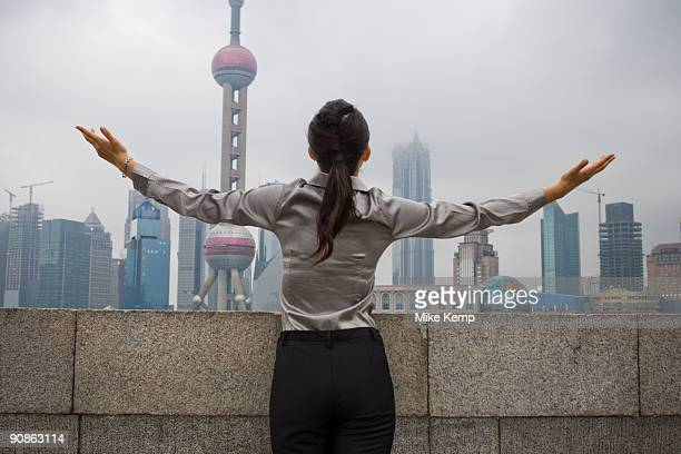 Businesswoman outdoors with arms up and city skyline in background rear view