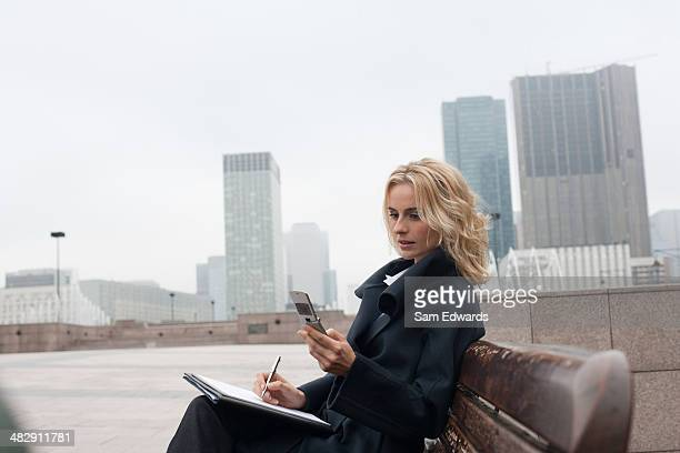 Businesswoman outdoors writing in notebook with celluar phone
