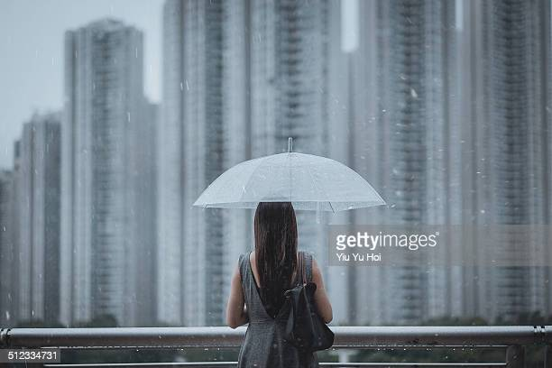 Businesswoman overlooking cityscape on a rainy day