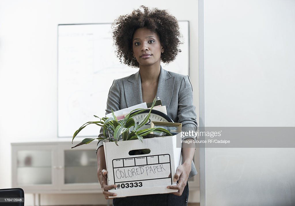 Businesswoman packing up box in office : Stock Photo