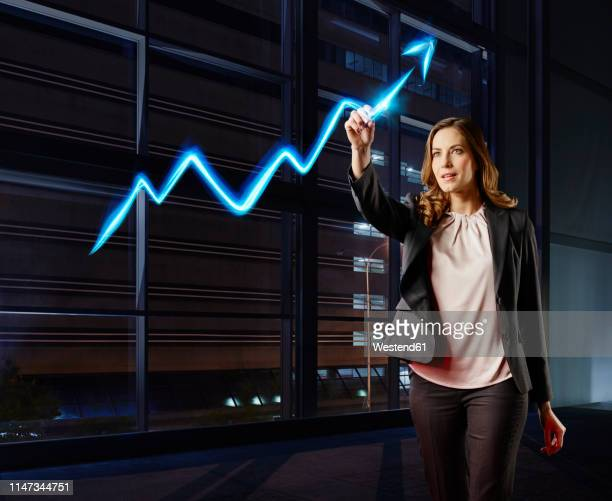 businesswoman painting the stock market development with light - bull market stock pictures, royalty-free photos & images