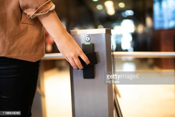 businesswoman passing by the turnstile - security stock pictures, royalty-free photos & images