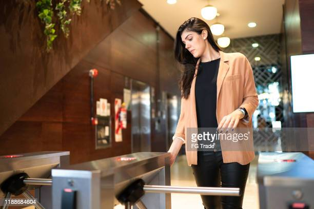 businesswoman passing by the turnstile - moving past stock pictures, royalty-free photos & images