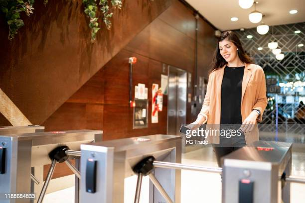 businesswoman passing by the turnstile - building entrance stock pictures, royalty-free photos & images