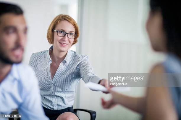 geschäftsfrau übergibt dokument an kollegin - ball passen stock-fotos und bilder