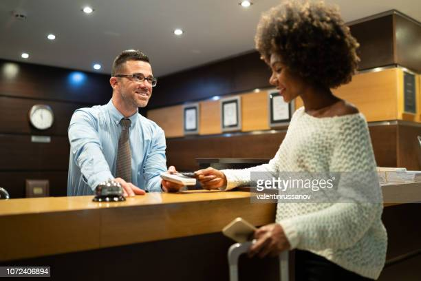 Businesswoman paying at hotel reception