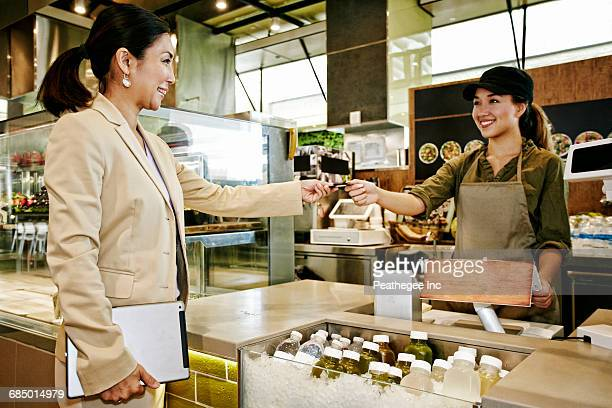 Businesswoman paying cashier in food court with credit card