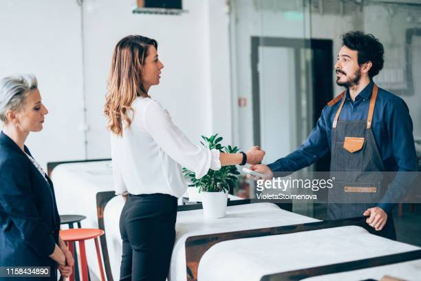 businesswoman paying contactless with smartwatch - money transfer stock pictures, royalty-free photos & images