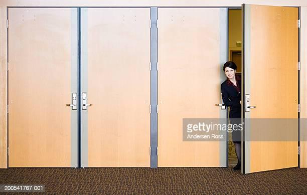 Businesswoman peeking head around door, portrait