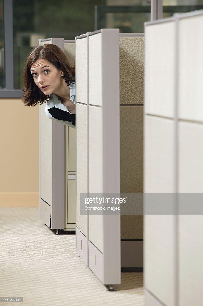 Businesswoman peeking out of cubicle : Stockfoto
