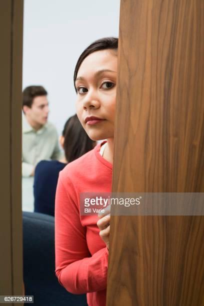 Businesswoman peeking out of office
