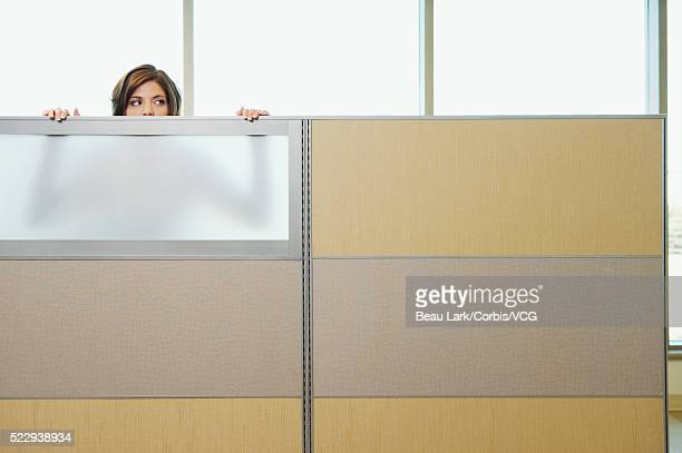 businesswoman peeking over cubicle wall - mid adult stock pictures, royalty-free photos & images