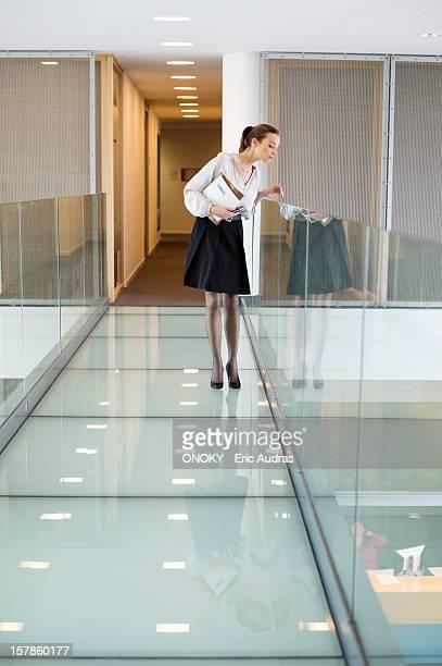 Businesswoman peeking through glass in a corridor