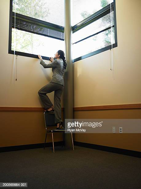 Businesswoman peeking through window, rear view