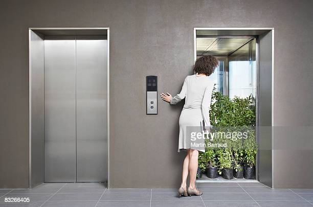 Businesswoman peering at elevator full of plants