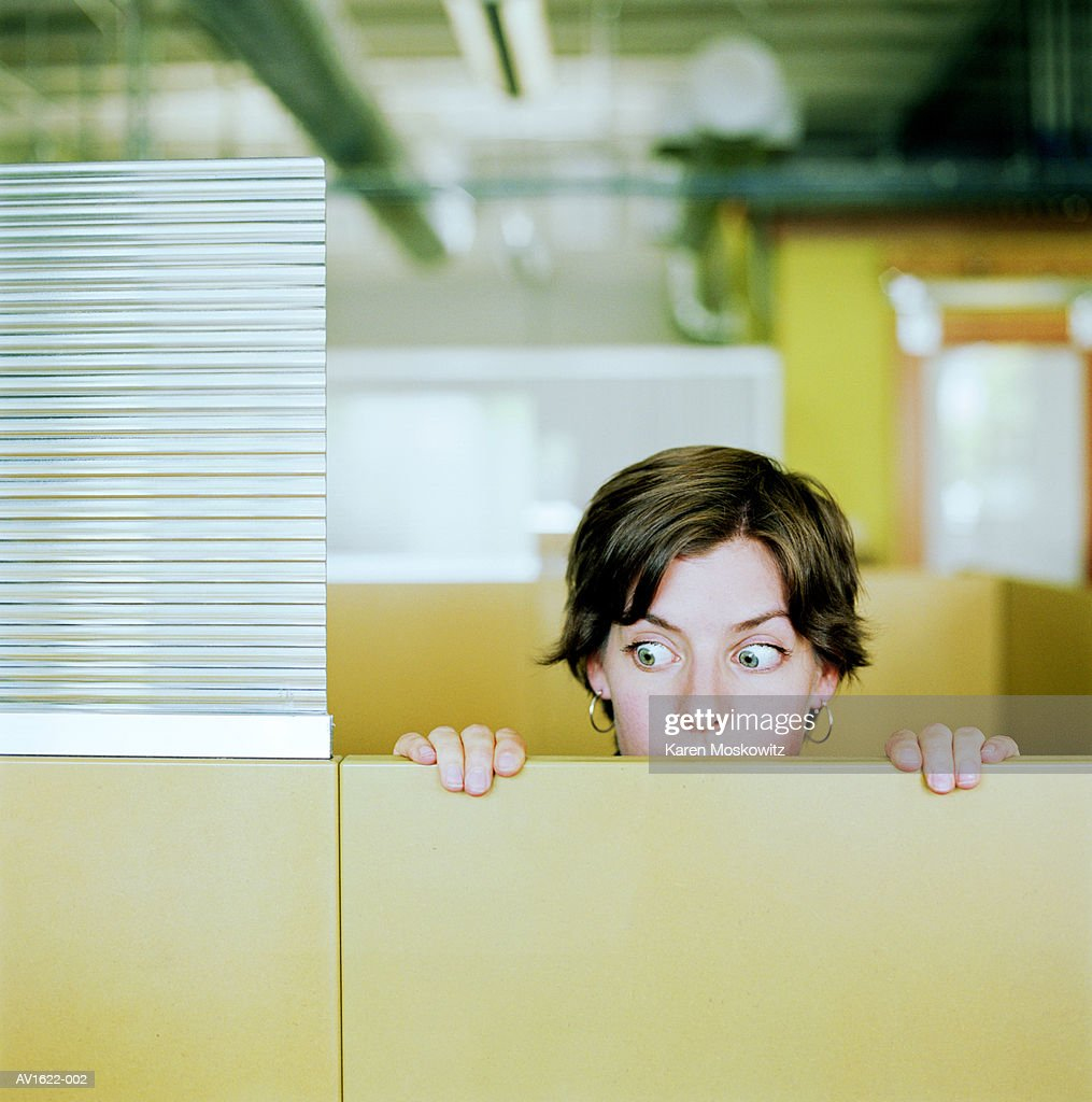 Businesswoman peering over cubicle wall : Stock Photo