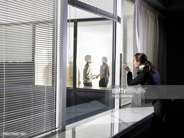 Businesswoman peering through blinds at people talking