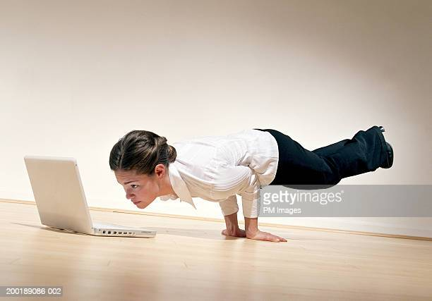 Businesswoman performing horizontal handstand, looking at laptop