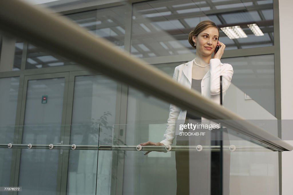 Businesswoman phoning with a mobile phone in an office building : Photo