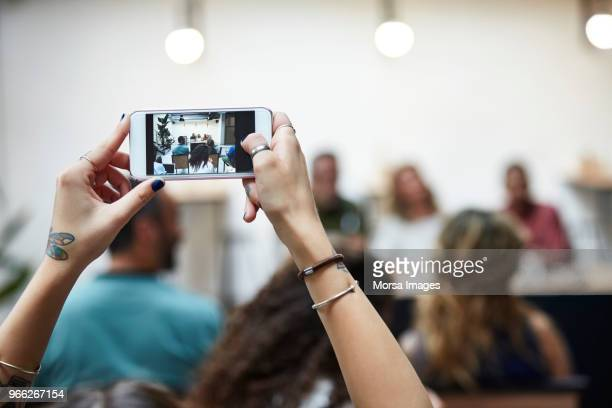 businesswoman photographing meeting during seminar - bracelet photos stock pictures, royalty-free photos & images