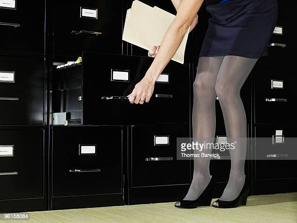 businesswoman placing folder in filing cabinet - mini skirt stock pictures, royalty-free photos & images