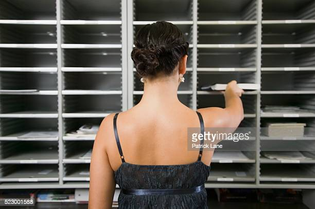 businesswoman placing mail in mailbox - spaghetti straps stock pictures, royalty-free photos & images