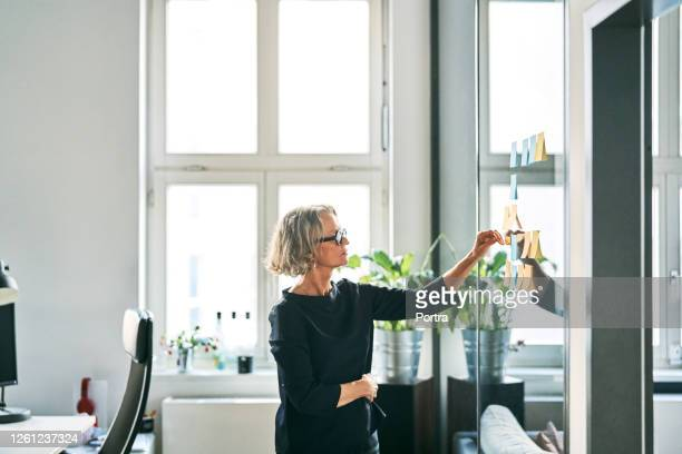 businesswoman planning over sticky notes - business finance and industry stock pictures, royalty-free photos & images