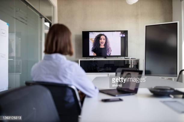 onderneemster die met een medewerker op videovraag plant - afgelegen stockfoto's en -beelden