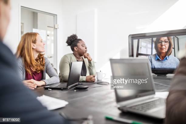 businesswoman planning with coworkers on video call - webinar stock photos and pictures
