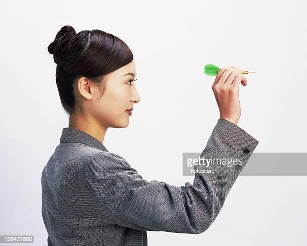 Businesswoman playing darts, Studio, Portrait