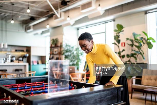 businesswoman playing foosball at coworking - one young woman only stock pictures, royalty-free photos & images