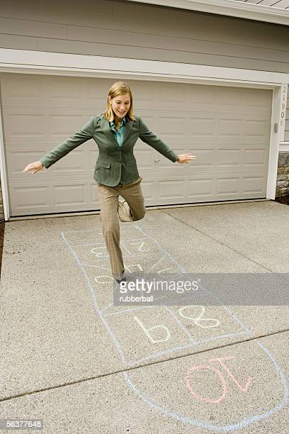 Businesswoman playing hopscotch