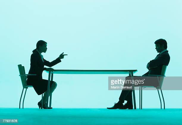 Businesswoman pointing at a businessman at a table
