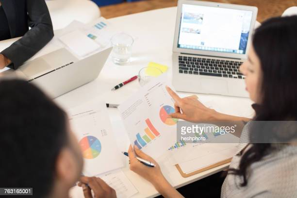 Businesswoman pointing at pie charts at conference table meeting