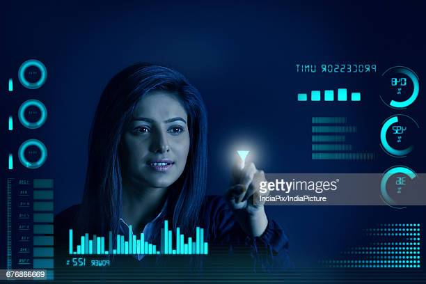 Businesswoman pointing down arrow, graphs and charts seen through screen