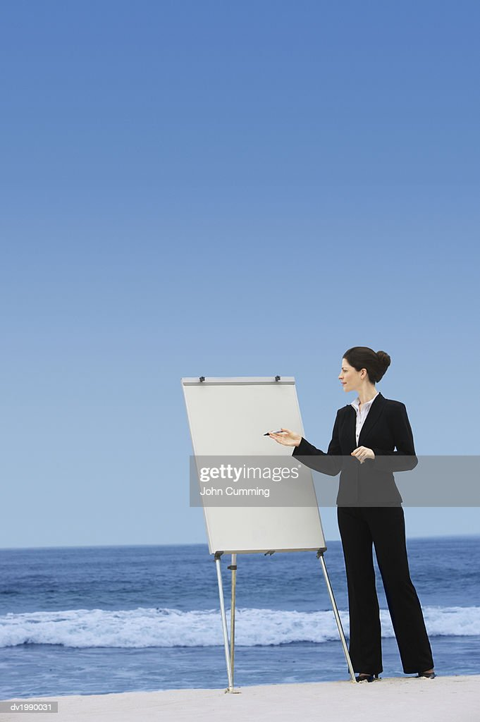 Businesswoman Pointing to a Blank Flip Chart on a Beach : Stock Photo