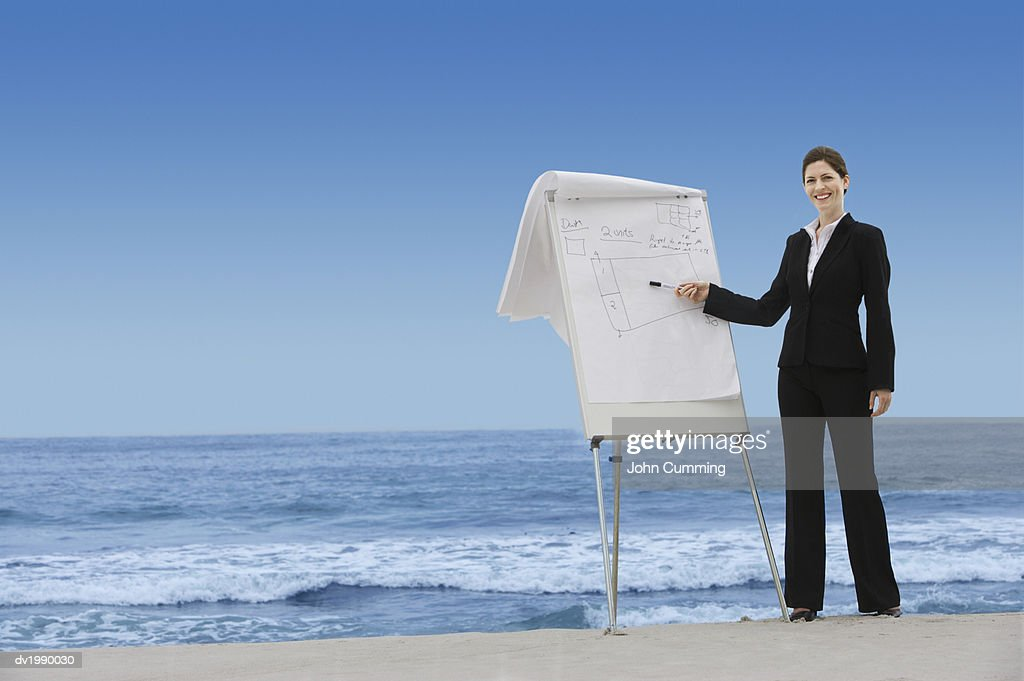 Businesswoman Pointing to Plans on a Flip Chart on a Beach : Stock Photo