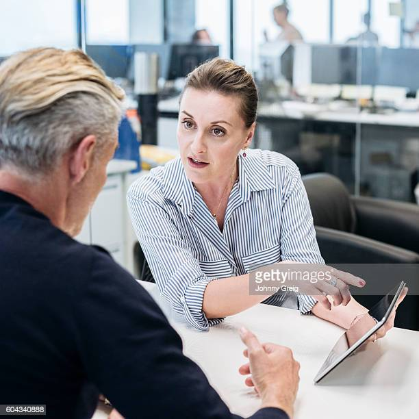 Businesswoman pointing to tablet and explaining to male colleague