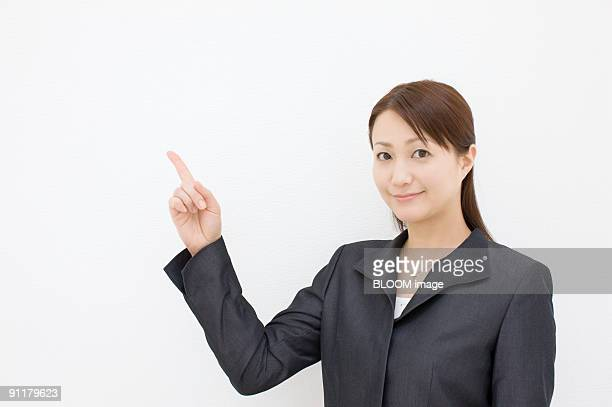 Businesswoman pointing upward, studio shot, portrait