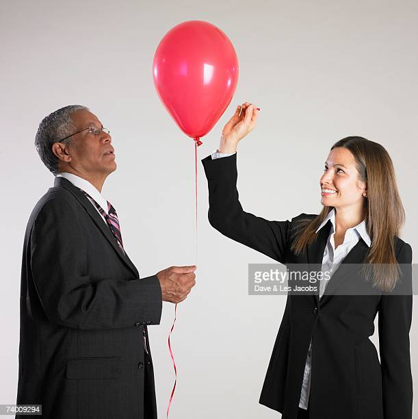 Businesswoman popping businessman's balloon