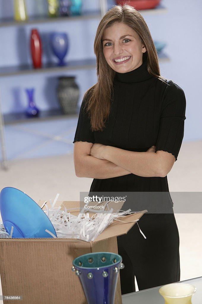 Businesswoman posing with open box in glassware store : Stockfoto